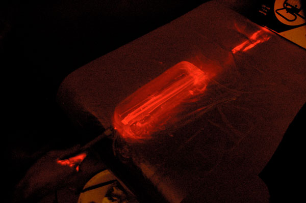 A laser is pointed into the gel, lighting it up.